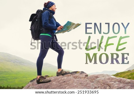 Woman standing on a rock holding map against enjoy life more - stock photo