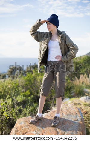 Woman standing on a rock looking to the distance in the countryside - stock photo