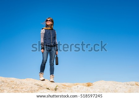 Woman standing on a rock with the wind blowing through her hair with a clear blue sky background