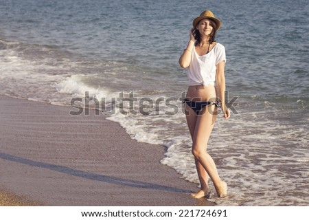 woman standing on a  sand seashore near sea looking on the water, relaxing on a vacation trip. copy space