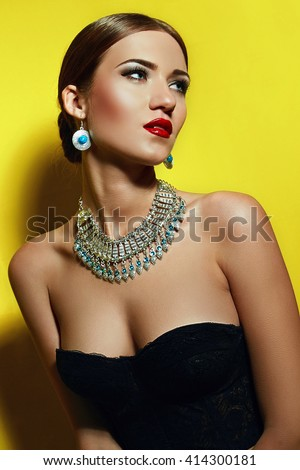 Woman standing on a yellow background. Dressed in a black corset. Necklace and bracelet. - stock photo