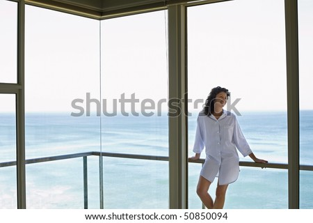 Woman standing on balcony, smiling