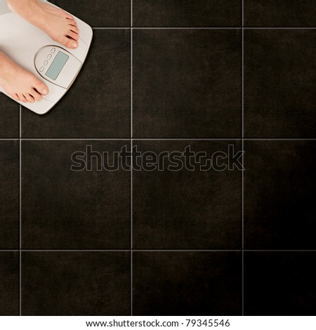 woman standing on bathroom scales on tiled floor