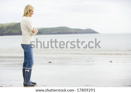 Woman standing on beach smiling - stock photo