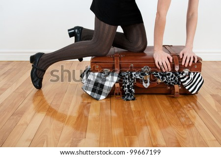 Woman standing on her knees on an overfilled suitcase with clothing. - stock photo