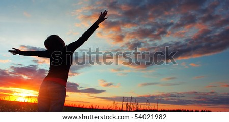 Woman standing on meadow with summer herbs over cloudy sky and sunset light - stock photo