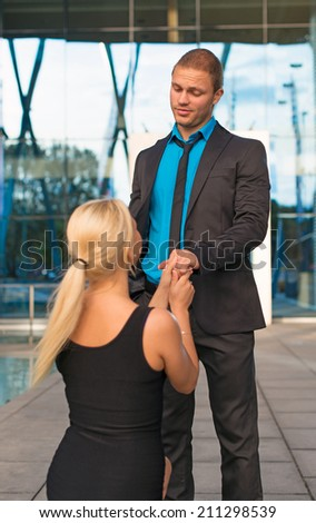 Woman standing on one knee and making proposal to man. - stock photo