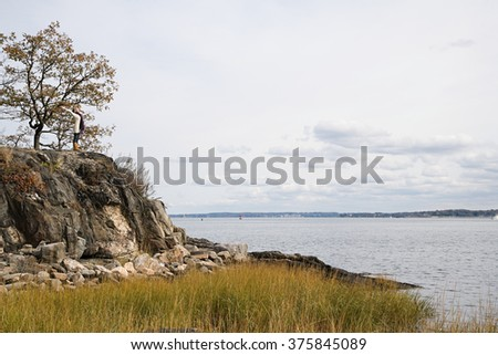 Woman standing on rocks near a lake