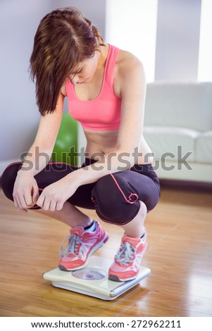 Woman standing on scales in front of a sofa - stock photo