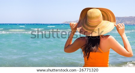 Woman standing on shoreline at the beach - stock photo