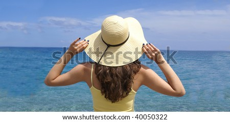 Woman standing on shoreline at the beach . Lots of copy space.