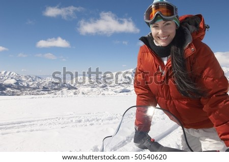 Woman Standing on snowmobile in snow, half length - stock photo