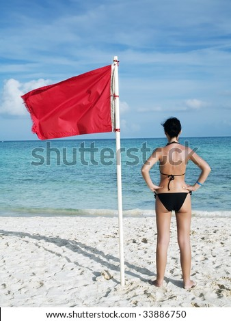 woman standing on te beach near a red flag on the sea meaning that swimming is dangerous and prohibite - stock photo