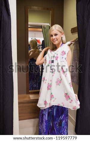 Woman standing on the changing room holding up dress - stock photo