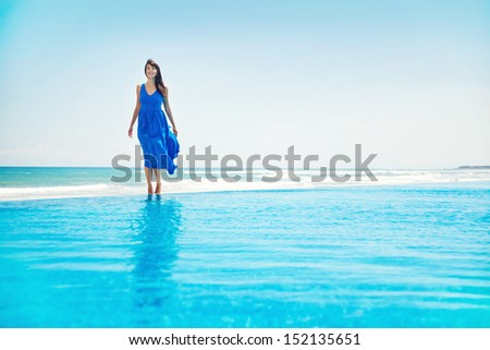 woman standing on the infinite water - freedom concept - stock photo