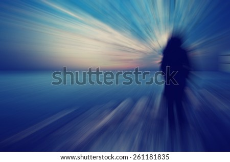 woman standing on the rocks watching sea sunset ,dramatic view,woman on the edge ,woman silhouette unusual ,outsider concept - stock photo