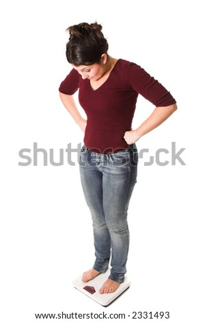 Woman standing on the scale with her hands on her hips looking surprised at the results - stock photo