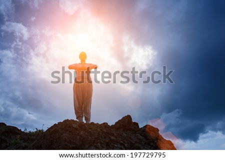 Woman standing on top of mountain doing yoga meditation. Stormy sky background, sun shining on her. - stock photo