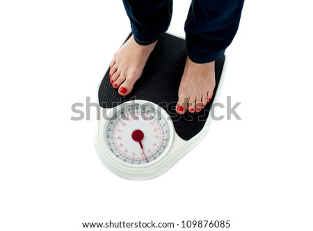 Woman standing on weighing scale, closeup of legs. All on white background