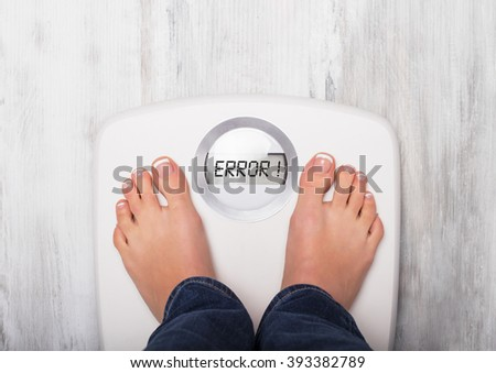 Woman standing on weight scale showing error message - stock photo