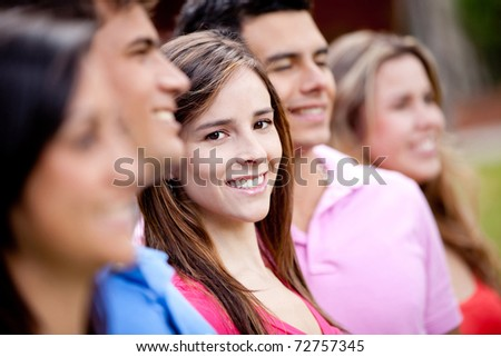 Woman standing out from a group of people and smiling - stock photo