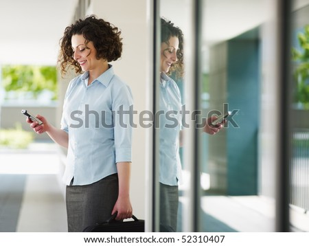 woman standing out of office building and reading emails on mobile phone. Horizontal shape, Copy space - stock photo