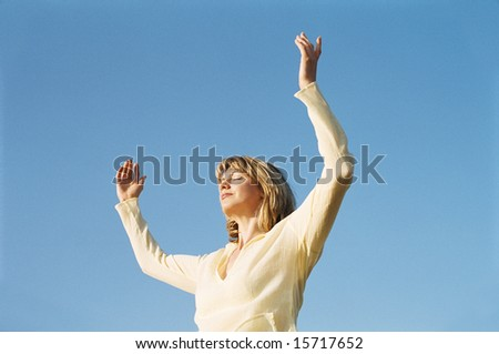 Woman standing outdoors with arms up - stock photo