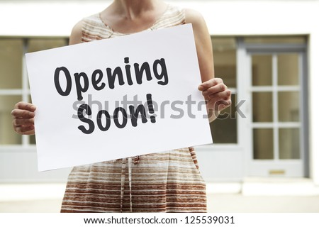 Woman Standing Outside Empty Shop Holding Opening Soon Sign - stock photo
