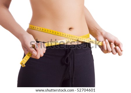 Woman standing pulling measuring tape around waist. - stock photo