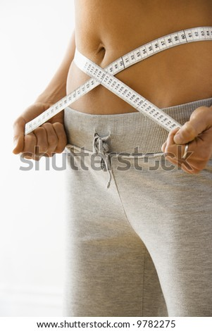 Woman standing pulling measuring tape around waist. - stock photo