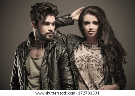 woman standing relaxed against her boyfriend and looks at the camera - stock photo
