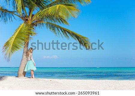Woman standing under palm tree on tropical beach - stock photo