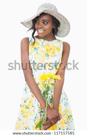 Woman standing wearing a floral dress while holding flowers - stock photo