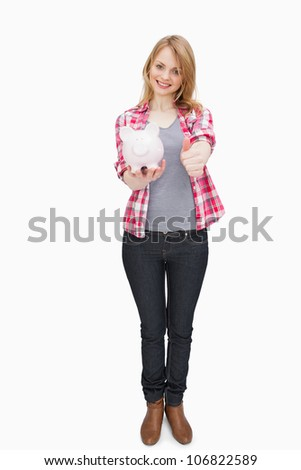 Woman standing while holding a piggy bank against a white background - stock photo