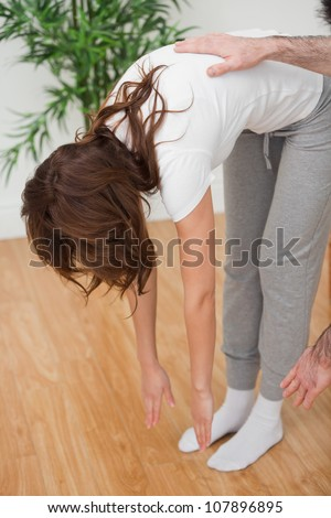 Woman standing while touching her feet with her hands in a room - stock photo