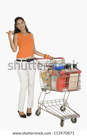 Woman standing with a shopping cart and pointing - stock photo