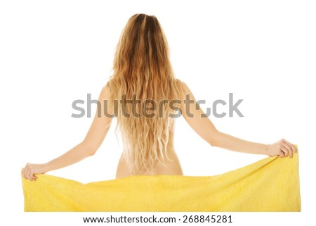 Woman standing with a towel back to camera. - stock photo