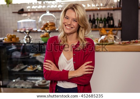 Woman standing with arms crossed in the cafe