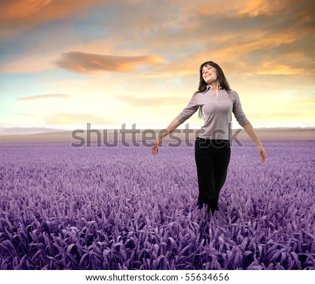 Woman standing with open arms on a lavender field - stock photo