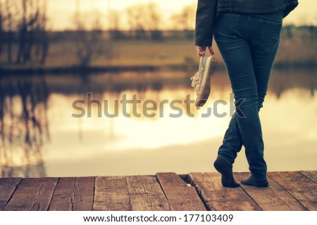 Woman standing with pair of retro shoes on pier