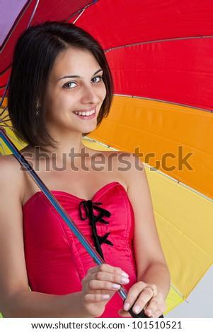 Woman standing with rainbow umbrella - stock photo