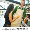 Woman standing with smiling store worker while holding drink bottle in grocery store - stock photo
