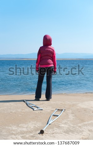 woman stands at shore having left her crutches, back view - stock photo