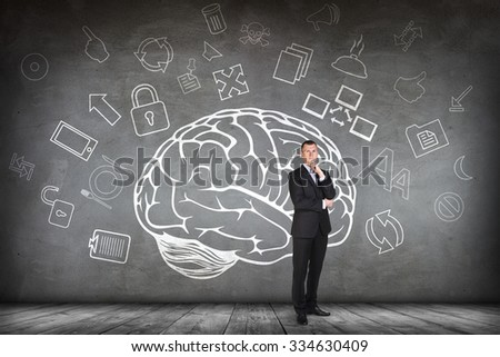 Woman stands beside big drawn brain on the gray wall - stock photo