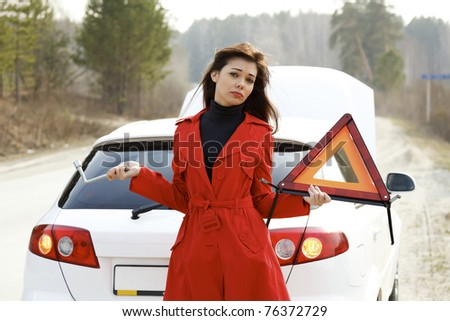 Woman stands by her broken car and holds red triangle and wrench in her hands - stock photo