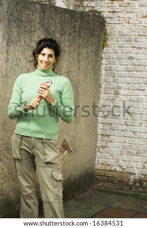 Woman stands holding pipe wrench. She is smiling at camera. Vertically framed photo. - stock photo