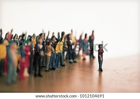 Woman stands in front of crowd or angry mob. Large group of people vs. one individual. Cyber bully concept or social media rage. One against many.