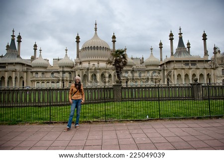 Woman stands in front of Royal Pavilion in Brighton, England - stock photo
