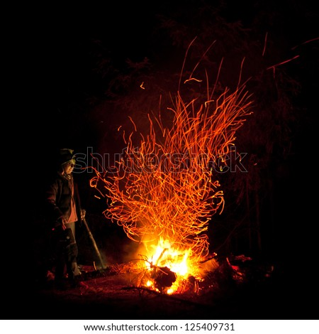Woman stands near firepalce with sparks in mountains in night