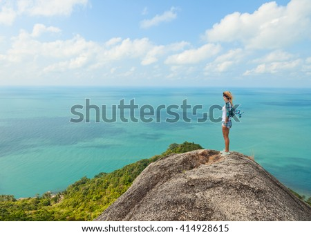 woman stands on a hill with stunning sea views. Travel, adventure, tourism concept. - stock photo